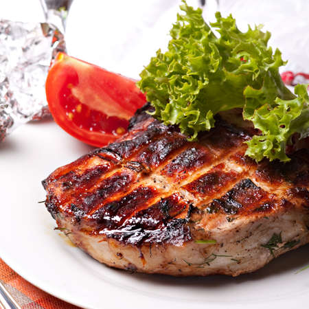 Grilled pork meat on plate with green salad