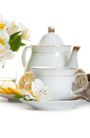 Cup of tea and teapot on table with flowers isolated over white Stock Photo - 14369992