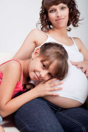 Pregnant woman with her daughter studio shooting photo