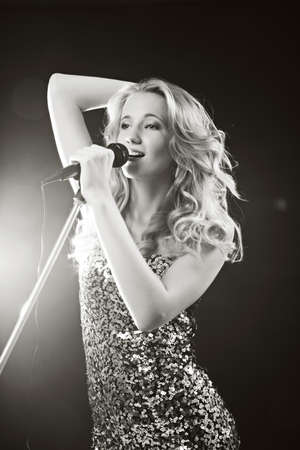 female singer: Portrait of an attractive teenager girl  singing with microphone. Black-white image