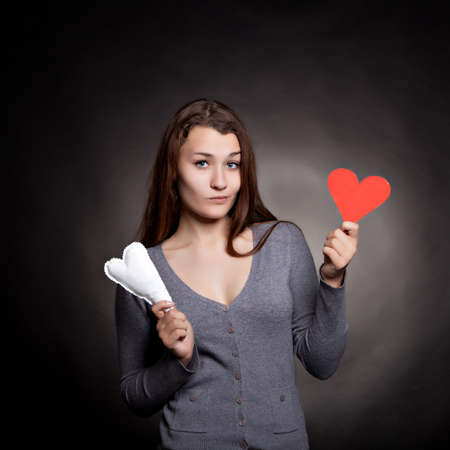 Young girl with two hearts on black background photo