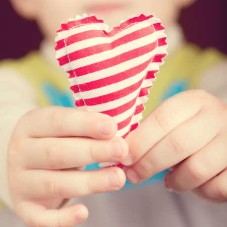 Kind hält Herz. Getönt