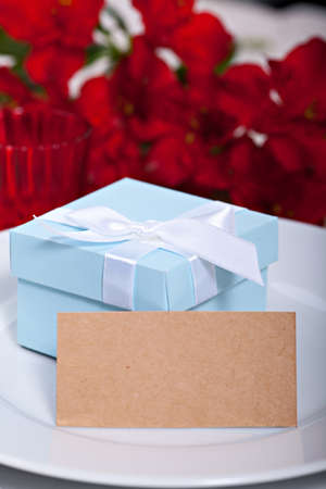Blue gift box on plate with blank card for your text photo