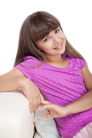 nude little girls: Красивая девушка, сидя на диване Фото со стока
