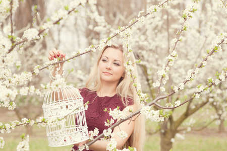 Beautiful blonde girl in spring in a blossoming garden with a decorative cage photo