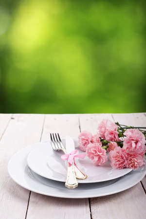 Plate with silverware on wooden table over green bokeh background photo