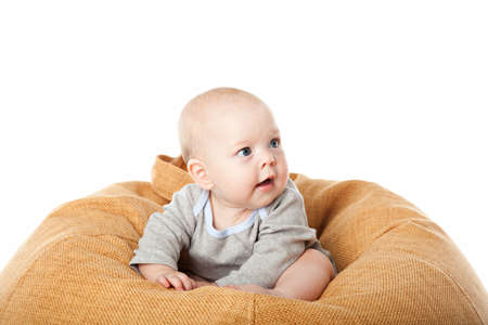 baby sit: Little baby boy sitting in bean bag chair isolated over white