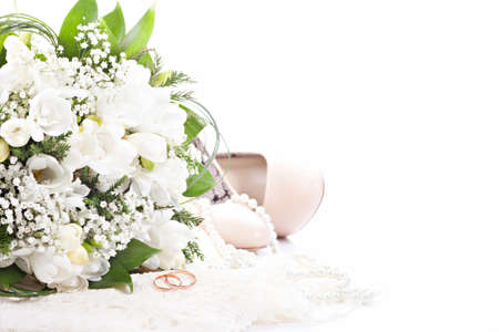 wedding accessories: Wedding rings on lace against wedding bouquet and shoes