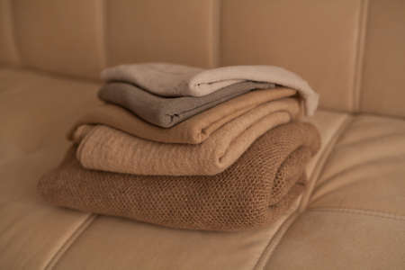 A stack of different fabrics of beige shades on the couch