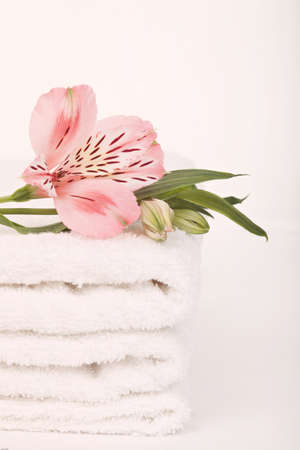 a stack of white soft towels decorated with a flower on white background