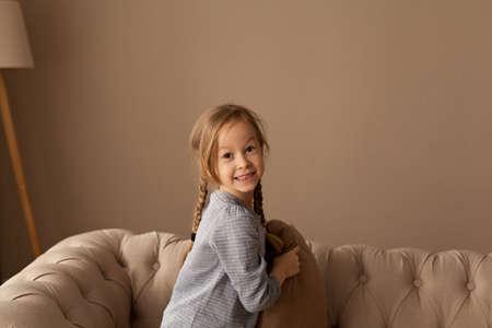Une fillette de sept ans joue à la bataille d'oreillers