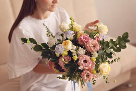 Girl's hands holding beautiful flowers bouquet on white