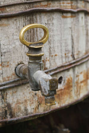 The old brass tap on the wooden cask photo