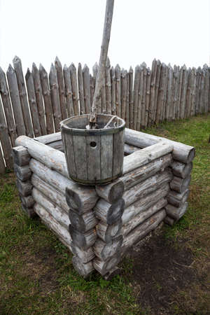 stockade: Wooden frame old well with a bucket on a background of a stockade isolated on white Stock Photo