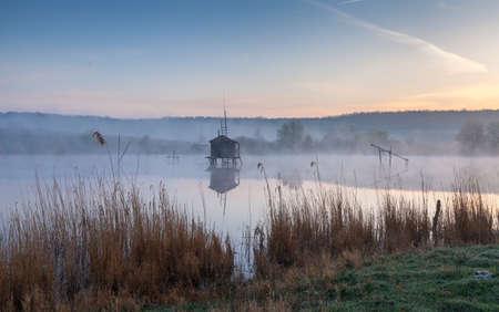 House of fisherman on a misty pond 版權商用圖片