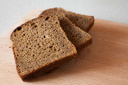 Pieces of porous brown bread sliced for eating