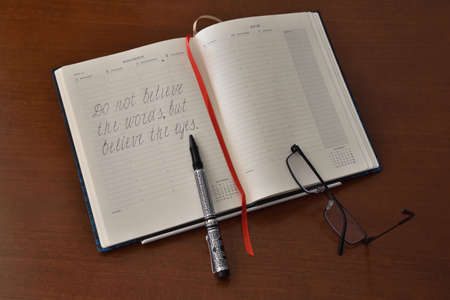 Open notebook with notes, pen and glasses on the table.