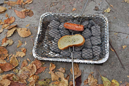 Autumn picture with a piece of white bread and a sausage over hot coals.