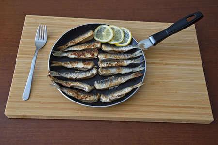 Fried herring in a pan with lemon.