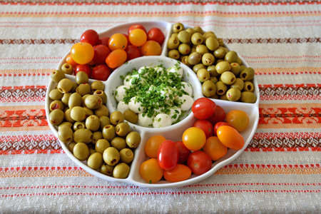 A plate with tomatoes, olives and mozzarella cheese, standing on the table.