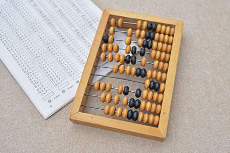 Abacus on a gray surface and a table with mathematical examples.