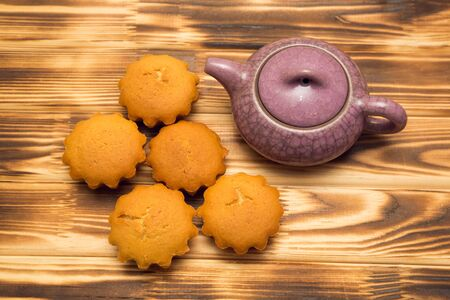chinesse: Cupcakes and a teapot on a brown Board