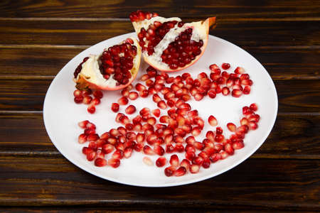 crimson colour: Pomegranate seeds and broken fruits on a white plate