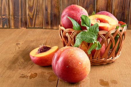 peaches in a wicker basket on a wooden table Stock Photo