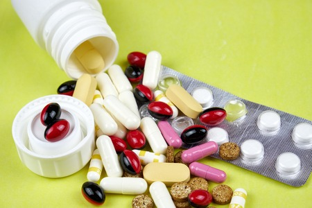 Open prescription bottles and white and yellow pills, tablets, vitamins, medicine, pills and drugs scattered on the yellow table. Pills for treatment and medicine. Stock Photo