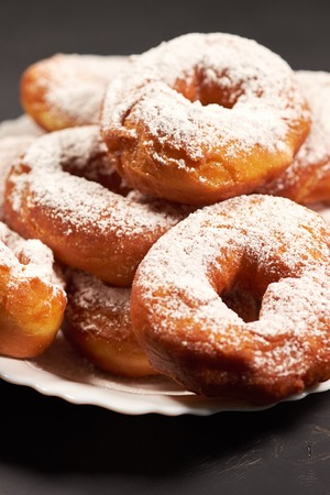 doughnuts sprinkled with powdered sugar on a white plate Banco de Imagens