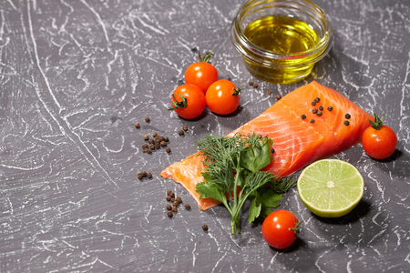 A piece of salmon on a gray background, tomatoes, dill, olive oil, lemon. Selective focus, space for text.