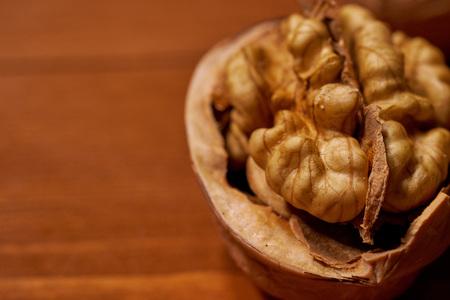 Walnut on brown wooden background.