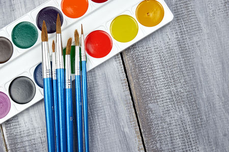 A palette of watercolor paints and brushes of different sizes, lying on a gray wooden background