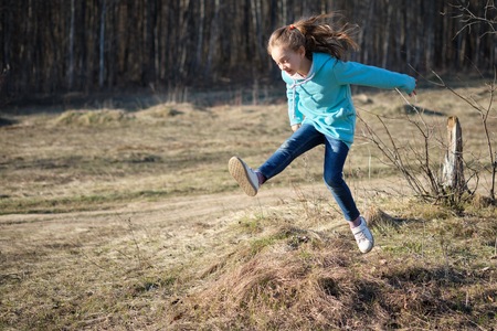 the girl in the turquoise blouse jumps into the spring woods