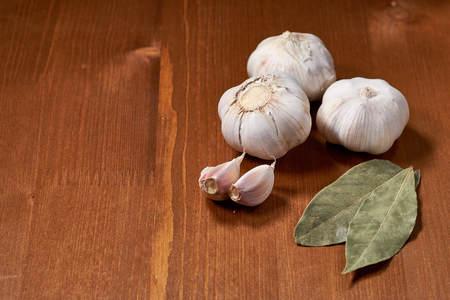 Garlic and garlic cloves on wooden background.