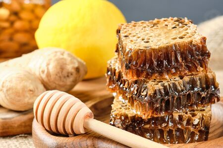 honey in honeycombs on a wooden plate. Jars with honey and almonds and hazelnuts in the background
