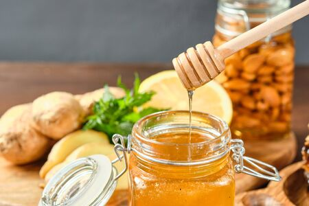 honey in honeycombs on a wooden plate and golden honey in a jar with nuts and comb for honey with lemon and ginger