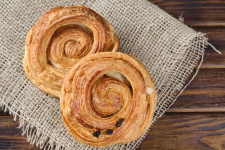 puff buns with jam and raisins in the shape of a snail on burlap and wooden background. Selective focus