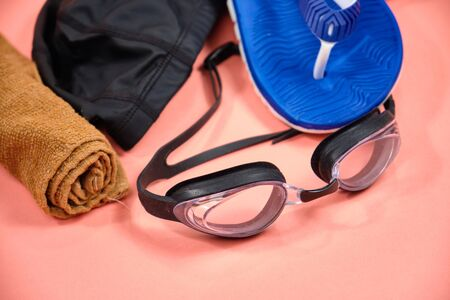 Accessories for swimming in the pool, glasses, cap, slates on a pink background Stock Photo