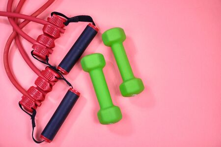 Fitness equipment, green dumbbells and a rubber expander with black handles on a pink background, space for text