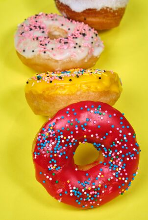 multicolored donuts on a yellow background, space for text