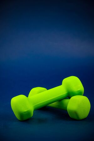 Green dumbbells lie on top of each other on a blue background