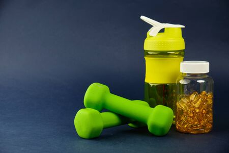 Plastic shaker, green dumbbells and a can of omega 3 on a blue background