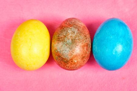Multicolored, painted Easter eggs on a pink background.