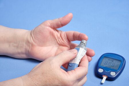 A woman makes a blood test for sugar, on a blue background. 스톡 콘텐츠