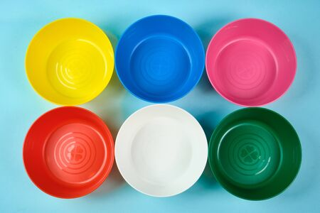 Multicolored plastic dishes on a blue background. The concept of environmental pollution by plastic, ecology. place for text,