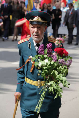 The veteran of operations with flowers on parade to the Victory Day in the Second World War in Pyatigorsk (Russia)