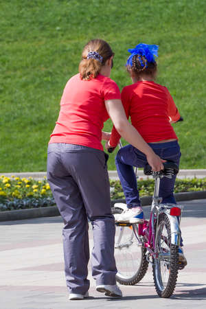 Mother teaches the daughter to ride a two-wheeled bicycle photo
