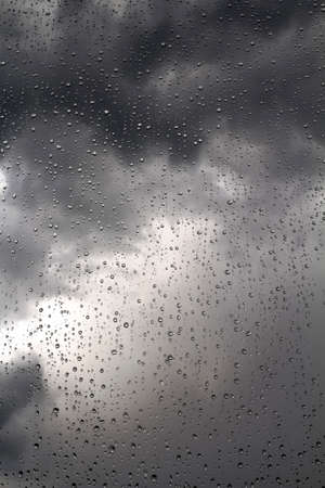 glass texture: Black stormy sky and rain drops on a window, background