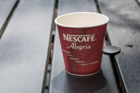 nescafe: PYATIGORSK, RUSSIA - AUGUST 11, 2014: Empty disposable glass of Nescafe with an advertizing slogan in Russian: Take hot, fragrant invigorating drink with itself!